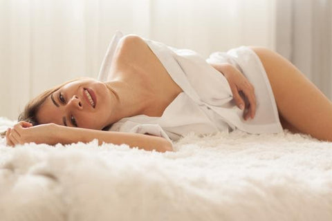 Woman laid on bed in white shirt