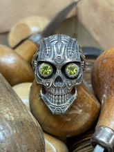 Load image into Gallery viewer, This is Peridot Skull Ring in Sterling Silver with intricate detail, looking like something straight out of Terminator. The Peridot eyes make this piece really pop when sparkling in the light