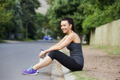 Woman sitting on side of road with water bottle in hand after finishing workout