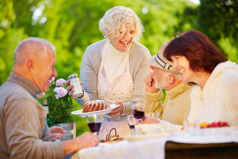 Older men and women enjoying dinner outside.  One older woman holding a cake in one hand and powdered sugar in the other.