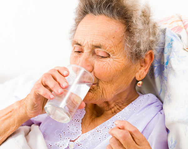 Senior woman taking supplements with glass of water