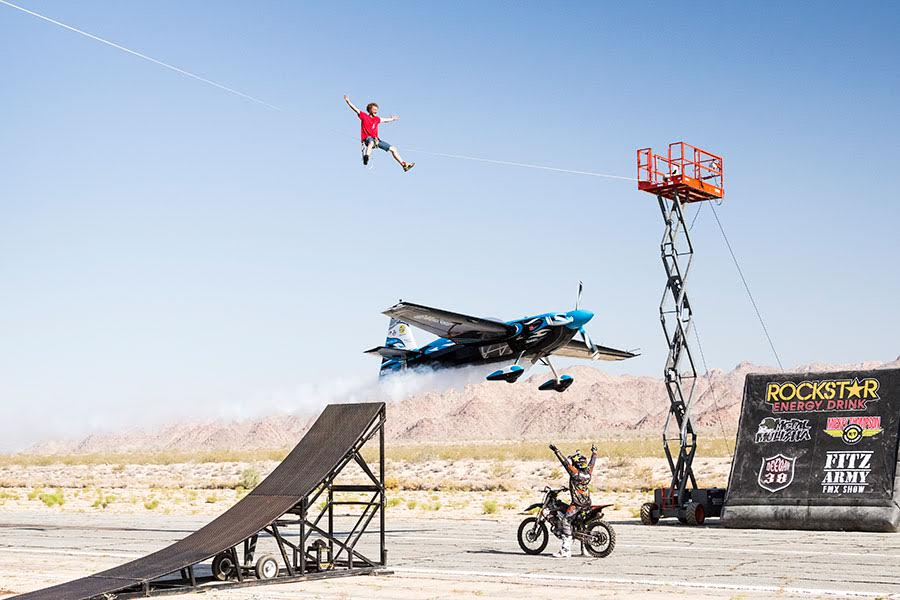 Stunt photo with tightrope walker, dirt bike, and airplane