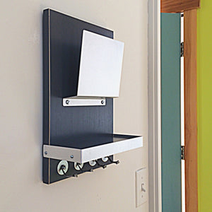 Black mail holder mounted on the wall. The black of the wooden body gives good contrast with the metal mail holder, key hooks and shelf border.