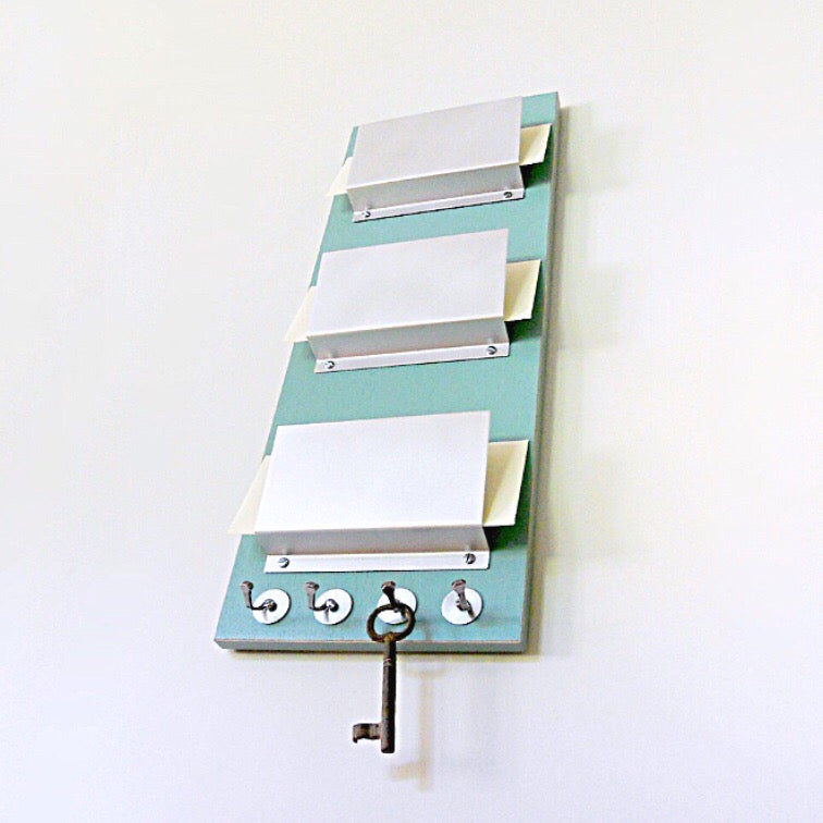 Mail holder piece titled RUE mounted on the wall. This piece includes three holders and key hooks at the bottom. The color of the piece is Soda.