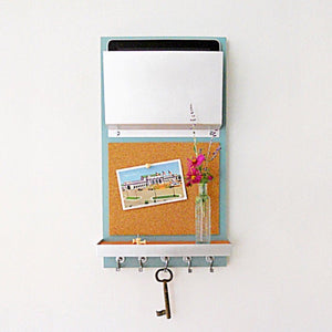 Light blue organizer with key hanging on hook from underneath and a post card on the cork board.