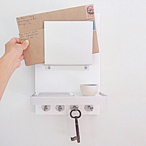 All white mail holder mounted on the wall with an iphone and flower pot on the shelf.