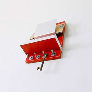 Angled shot from below of the red mail holder showcasing the key hooks and attached wooden shelf with metallic border walls.