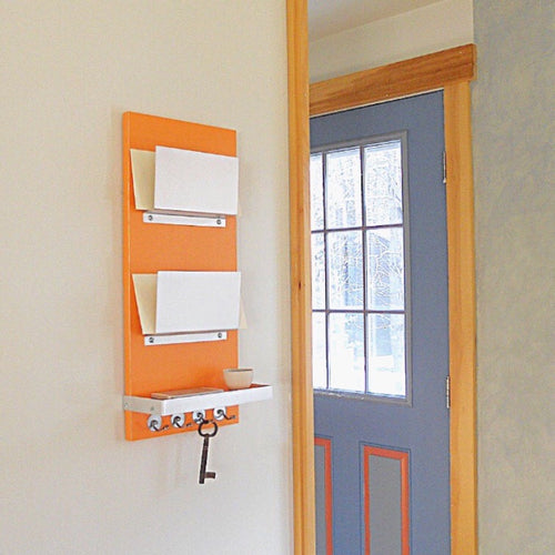 Double mail holder piece titled Voltage in the orange colorway. This piece has two metal orgainzers one below the other and a wooden shelf with an aluminum rim around the shelf as well as key hooks at the bottom.