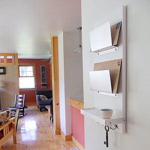 White double mail holder mounted on the wall.