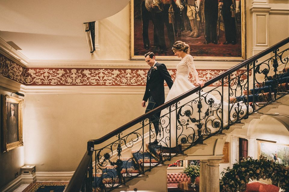 A bride and groom on their wedding day, descending a grand staircase