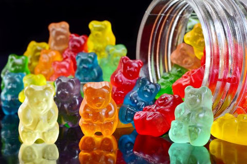 A bunch of weed gummy bears spill out of a jar