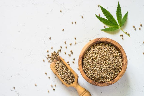 A spoon, bowl and table covered in cannabis seeds.