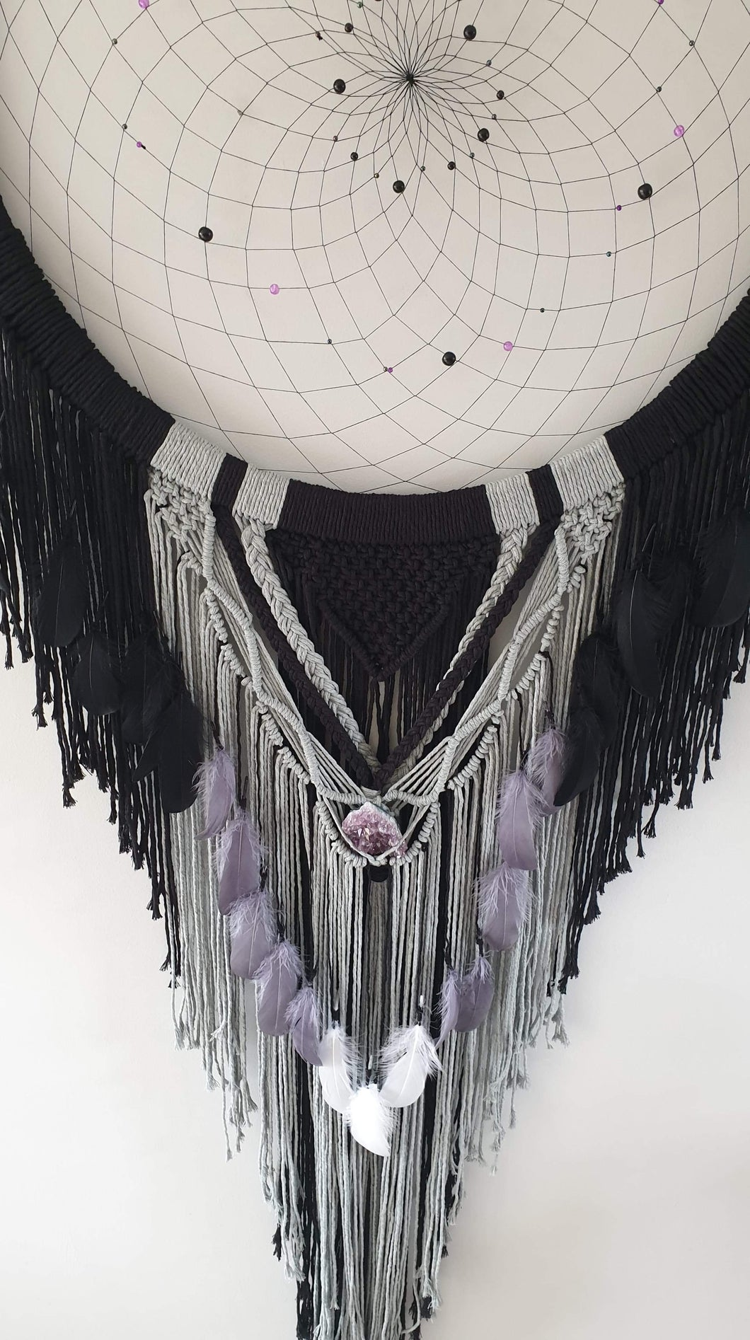 Handmade black and grey dreamcatcher with crystal and feather detail.