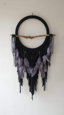 Black dreamcatcher with driftwood and feathers