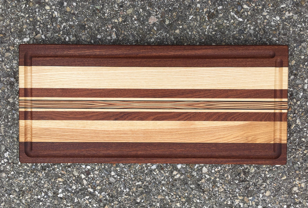 Multicolored chopping board. Different wood essences harmoniously asembled with a middle line figuring a sublime curved marquetery.