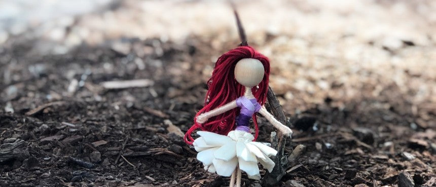red hair fairy leaning against a tree