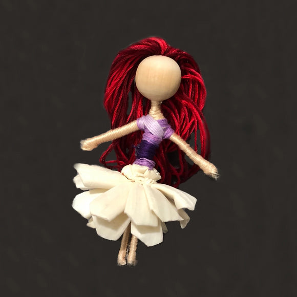Dahlia from front showing red hair, purple shirt and raw flower skirt