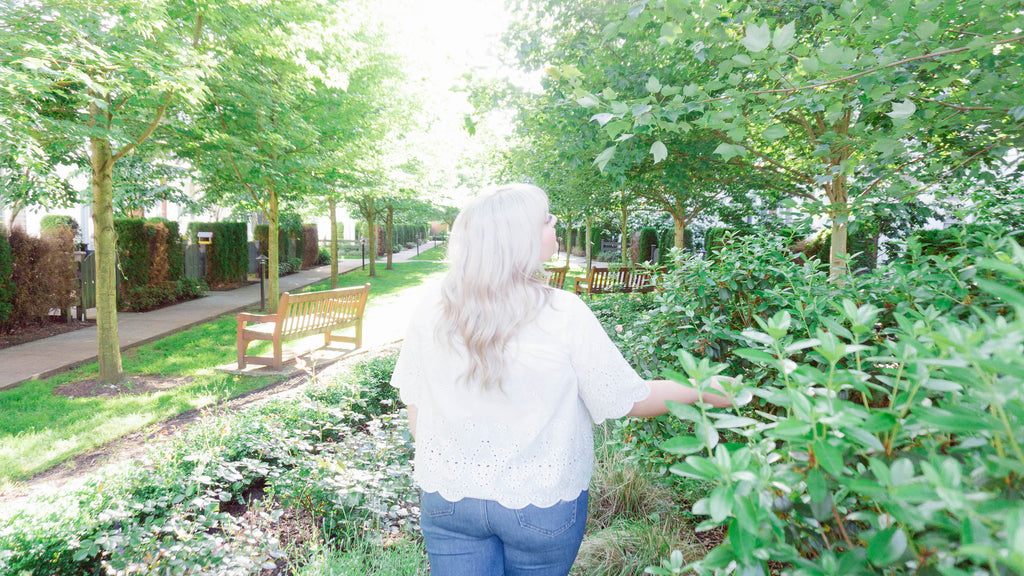 Woman with platinum blonde hair walking through trees and bushes wearing lightweight white top and jeans
