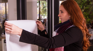 Woman sticking an electrostatic charged dry erase sheet (SmartSheets) to a glass surface