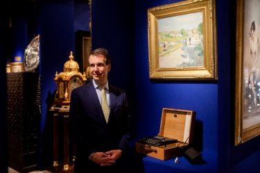 Bill Rau, head of M.S. Rau antiques, standing next to the Enigma machine that he was selling for $198,500 at an art and antiques fair in New York. Credit Sam Hodgson for The New York Times