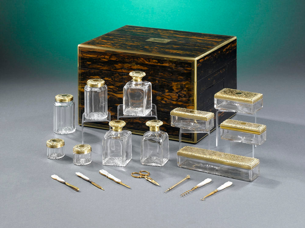 An elegant English nécessaire de voyage is veneered with rich coromandel wood with brass inlay and houses several crystal jars and other toiletries. Dated 1863.