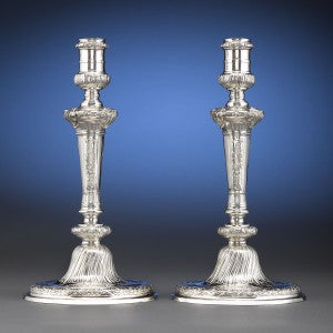 Crafted by Alexander Johnston, these candlesticks deeply chased decoration in a well-balanced design