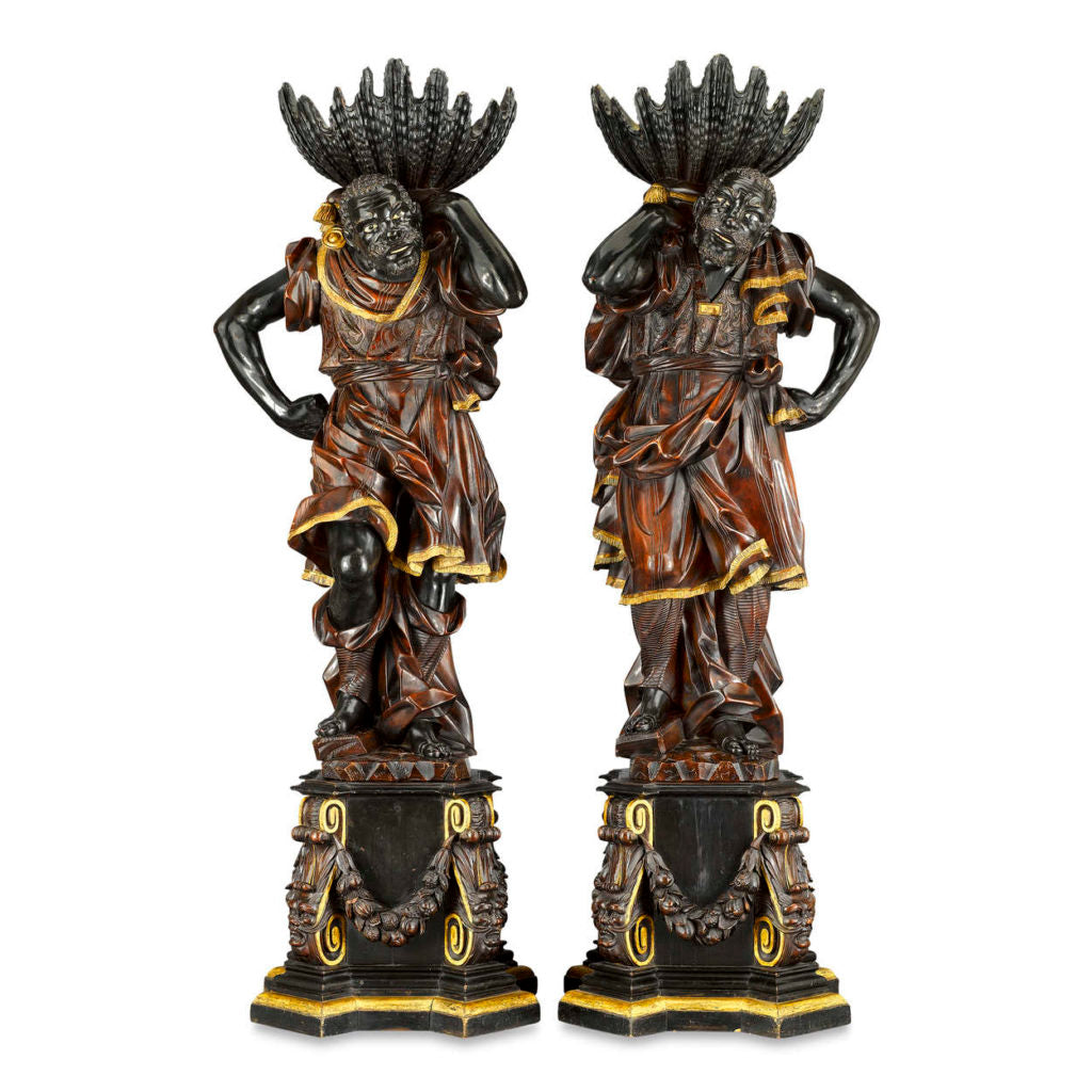 A pair of ebonized, painted and gilded blackamoor jardinières, circa 1850.