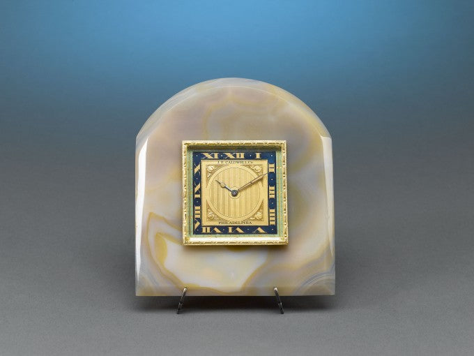 The dial is framed by a luxurious plaque of amber-hued onyx