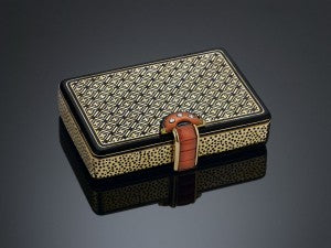 This 18K gold case features two compartments and a sliding coral and diamond latch