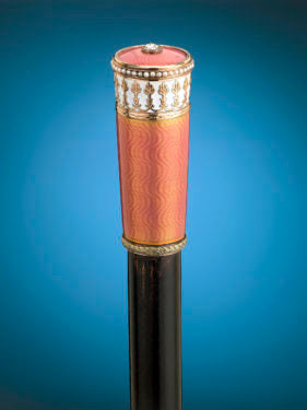 Enveloped in translucent salmon enamel, this walking stick outlines Fabergé's perfection of the enameling process
