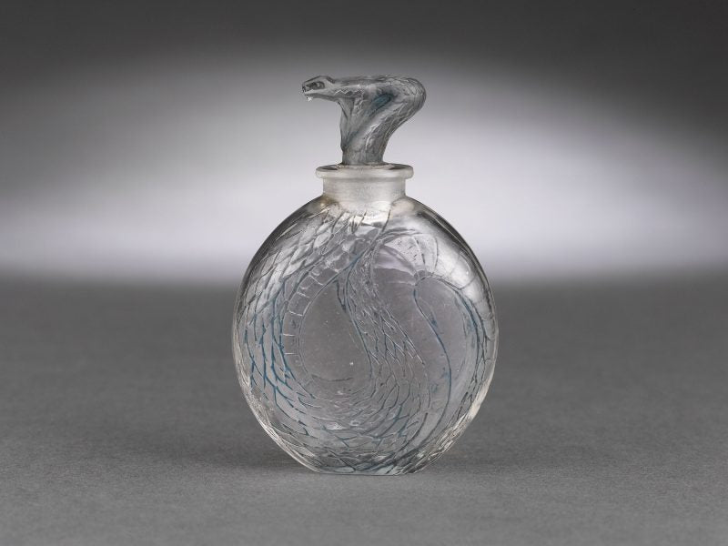 An elegant viper wraps itself around this incredible Lalique Serpent art glass perfume. Circa 1920