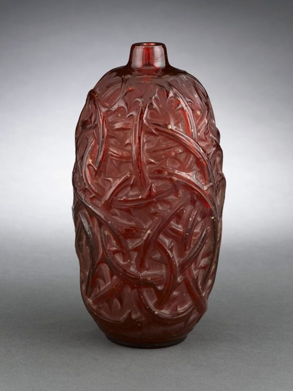 This stunning crimson art glass vase was created by the legendary René Lalique, circa 1913-21. Entitled Ronces, the bold design is engulfed by thorny briars