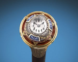 A ring of rubies surrounds the base of the knob, which is further accentuated by grisaille enamel plaques and golden guilloché enamel