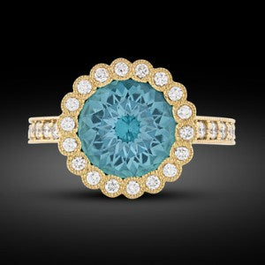 Exhibiting a deep turquoise blue hue, the stunning tourmaline is joined by approximately 0.51 carat of shimmering diamonds in its delicate 18k yellow gold setting