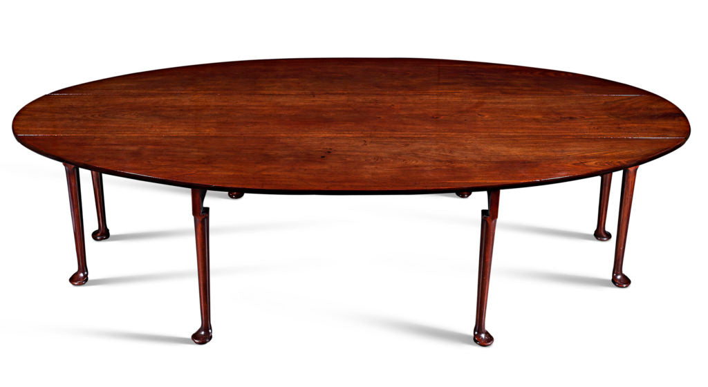 """Often referred to as an Irish """"wake"""" table, this extra-long oval table would have once been used year-round as a dining table. Yet, it also would have served as the focal furnishing of a wake when a death occurred. Skillfully constructed with folding side panels, it could be used to display the coffin of the deceased before burial. Irish Celtic tradition mandated that the body of the recently departed be watched constantly to prevent its removal by evil spirits. This beautiful table would have been specially commissioned by an affluent Irish family as an important part of the final rites - as well as the final celebration of the lives of their loved ones."""
