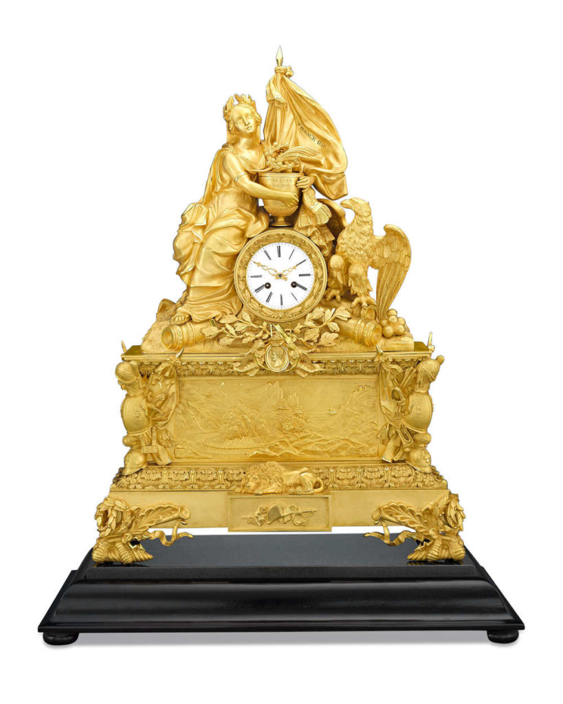 """A mantle clock made to commemorate theretour des cendres, or """"return of the ashes"""" to France. Rife with symbolism, it includes the French flag with the date 1840 on it (the year Napoleon's remains were returned), the figure of Mother France holding an urn marked """"May 5th, 1821"""" (the date of the emperor's death), and a detailed relief showing the ship leaving St. Helene and coming to Paris."""