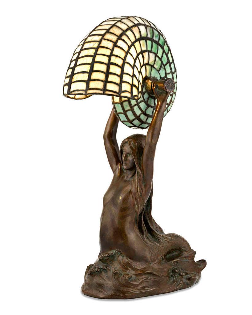 A mermaid rises from the sea presenting a mosaic glass nautilus shell that serves as a desk lamp. By Louis Comfort Tiffany circa 1905