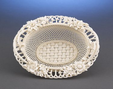 Carefully formed with a four-strand woven base, this Belleek basket features delicate twig handles and radiating latticework