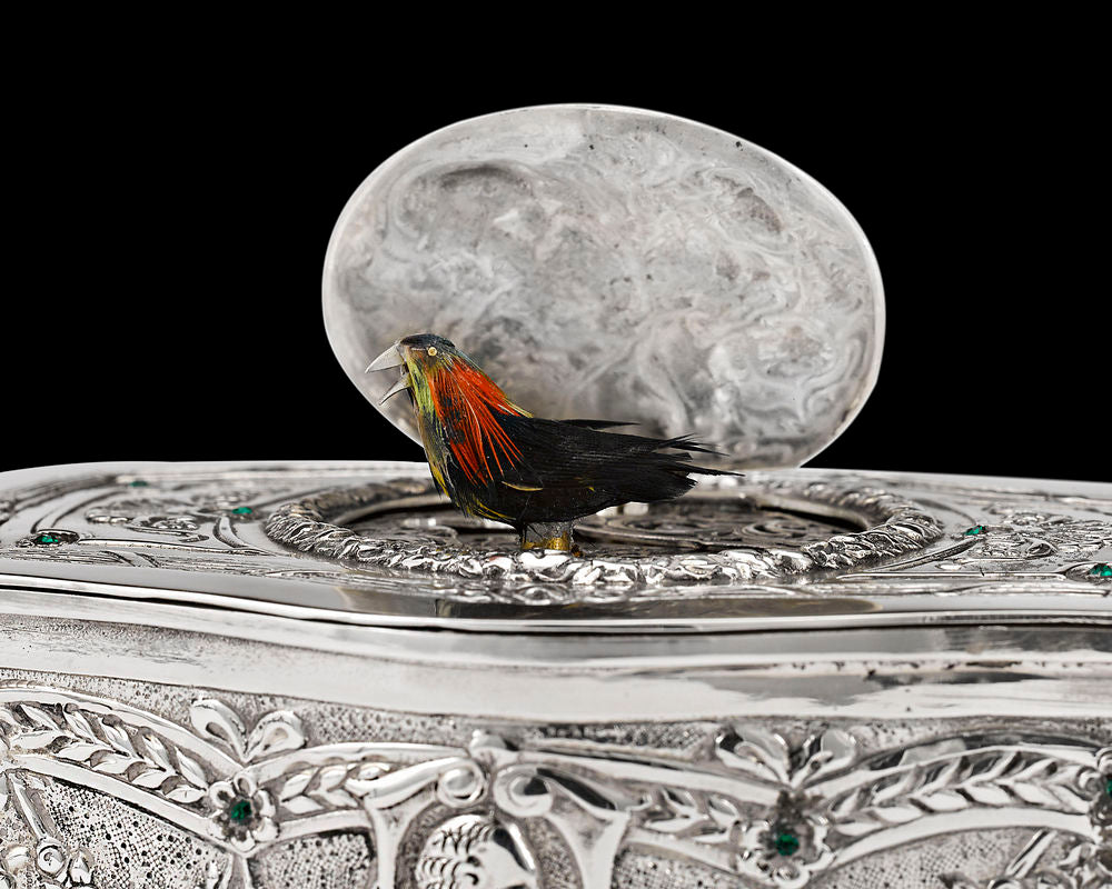 The hand-feathered automaton bird in a rare 19th-century Continental silver singing bird box.