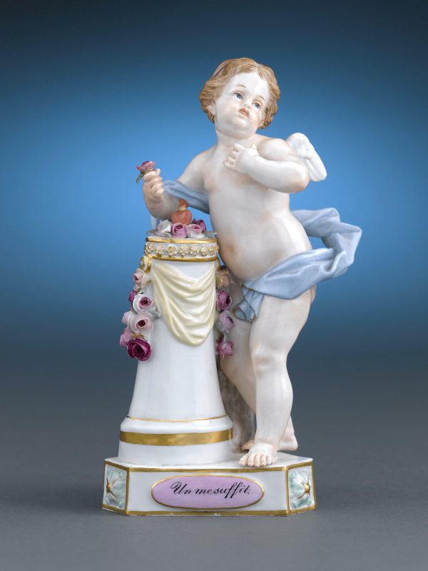 "Part of the company's beloved ""Cupid Mottos"" or ""Devise Children"" series, cupid admires a single flaming heart with the motto ""Un me suffit"" (""One is enough"") inscribed on the base"