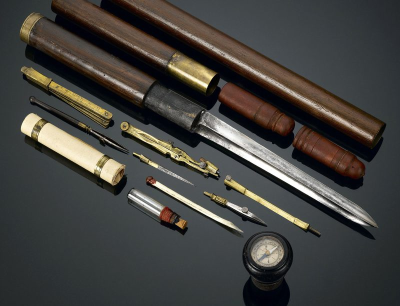 A small compass is set into the knob handle, while several more instruments are tucked inside the shaft, including a telescope, a bayonet, a drafting compass, pens and parchment papers, field maps, and plotting tools