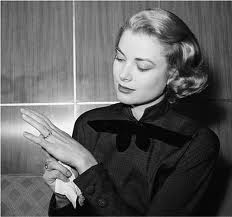 Grace Kelly admiring the elegant ruby and diamond eternity band Prince Rainier III initially gave as the engagement ring.