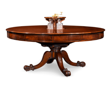 The center of the table lifts to reveal a crystal decanter service.