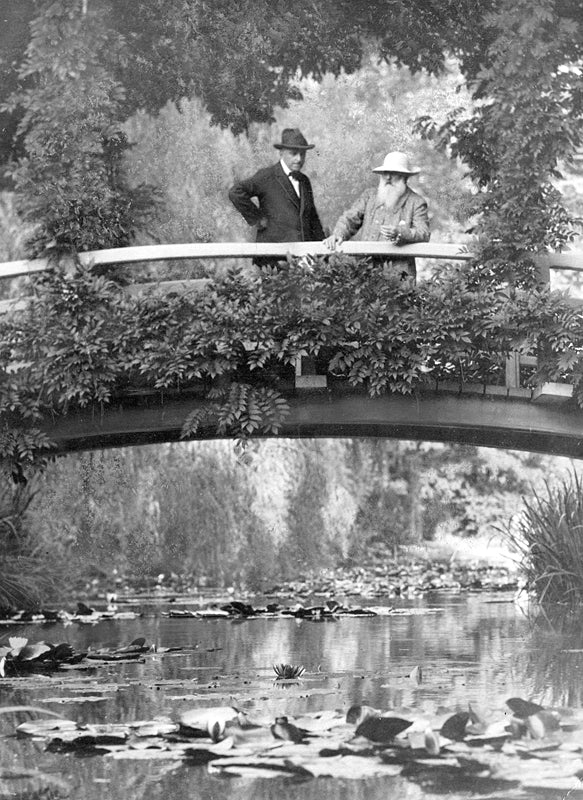 Monet (right) surveys his gardens from his Japanese bridge with an unknown companion in 1922.