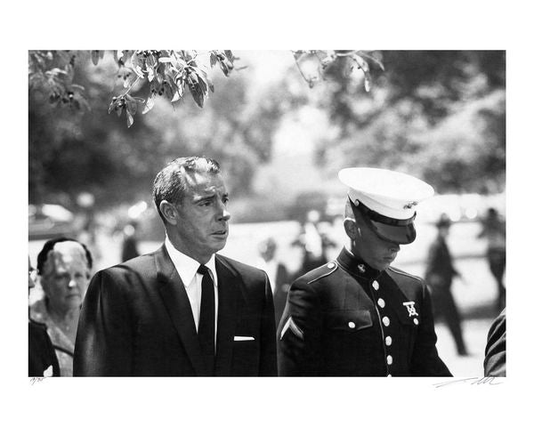 Monroe's ex-husband, Joe DiMaggio, is captured in a somber and tender moment at Monroe's funeral, August 8, 1962