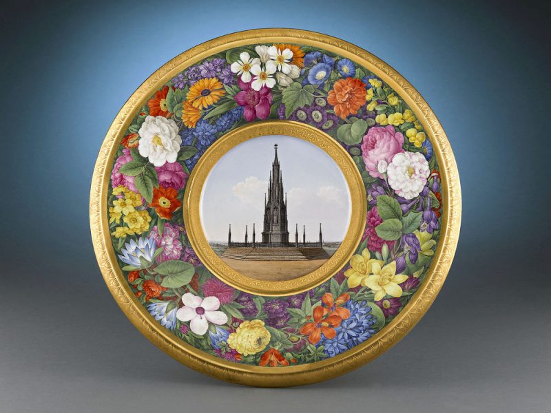 "This ""peace dish"" is hand-painted with the Monument surrounded by an intricate bouquet of flowers"