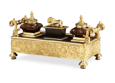 Bronze ormolu is contrasted by cranberry cut glass in this Regency-period inkwell