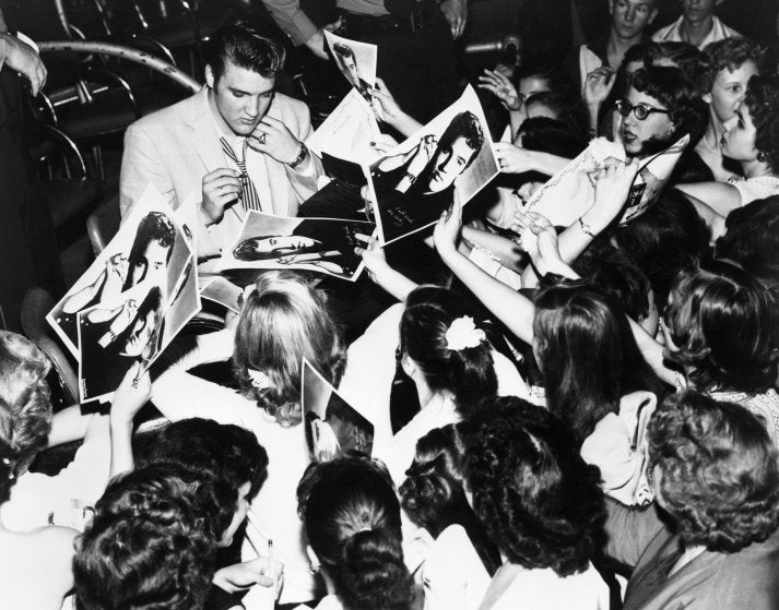 Elvis is surrounded by his enthusiastic teenage fans in Houston, TX., 1956. Image: Bettmann/Getty Images