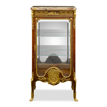 This vitrine in the Louis XVI style has the clean, elegant lines and right angles of the period, as well as exceptional marquetry in kingwood, simple ormolu ornamentation and a neoclassical-style depiction of a woman and an angel on the center mount at the bottom.