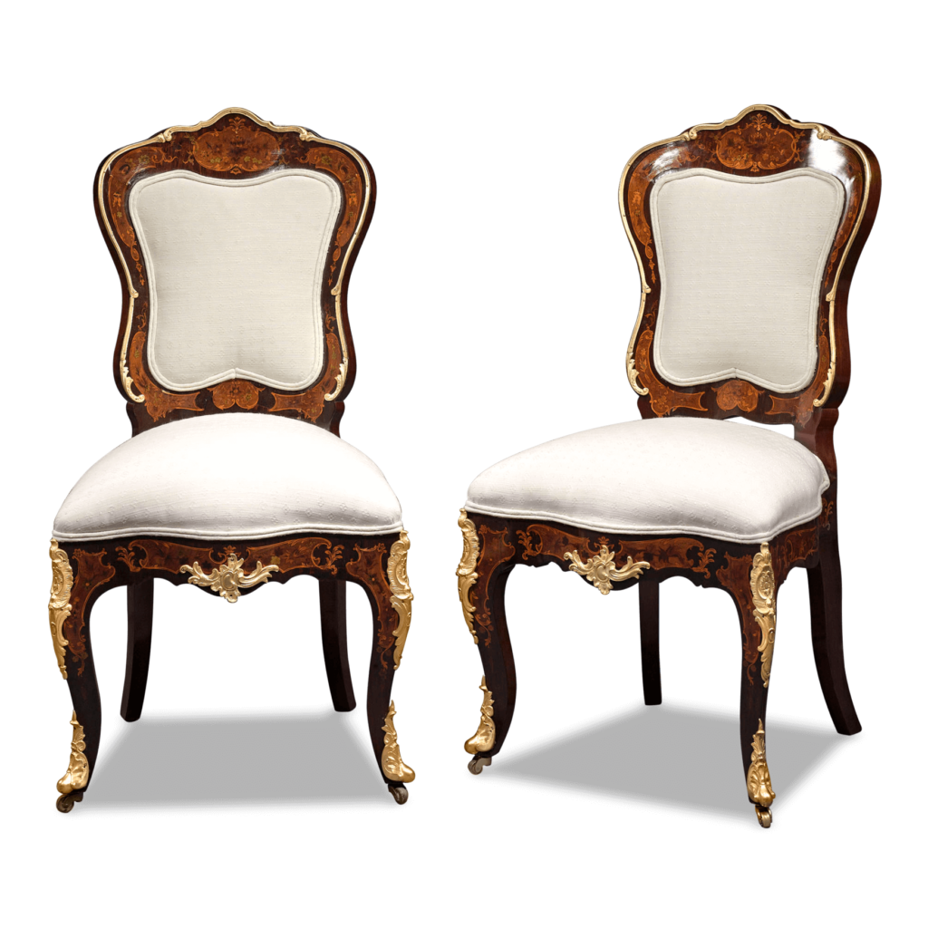 These magnificent chairs feature many notable Louis XV design characteristics, including plush upholstery, delicate exotic wood inlay in floral pattern, and elegant cabriole legs with doré bronze detail.